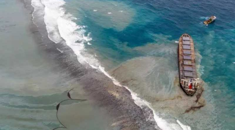 The Wakashio vessel aground on Pointe d'Esny's coral reefs with oil leaking from a crack. A floating oil boom can be seen drifting, a nearby tugboat is ready to intervene when the ship breaks, 10 August 2020. © Ashish K.
