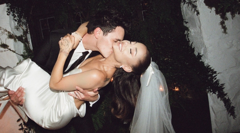 Ariana Grande in a white gown and veil being carried in a bridal position by husband Dalton Gomez, who is in a black suit with a white shirt and black tie.