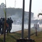 Banging pots, tear gas, in anti-COVID-19 protest