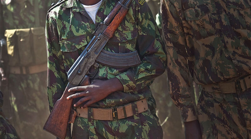 Mozambican soldier waits in line with an AK-47