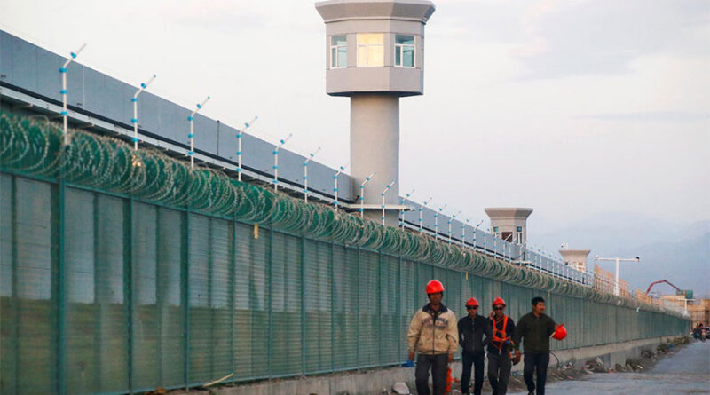 Workers walk by the perimeter fence in Dabancheng in Xinjiang Uighur Autonomous Region